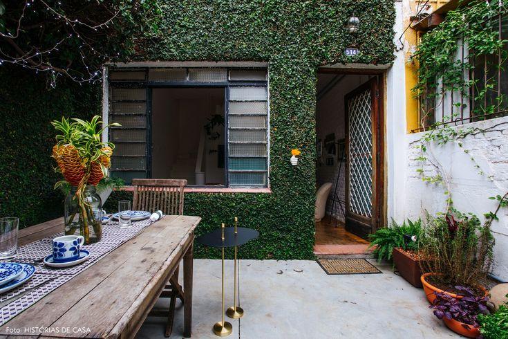 Jardim de casa tem mesa de madeira e vasos de barro com hortinha.