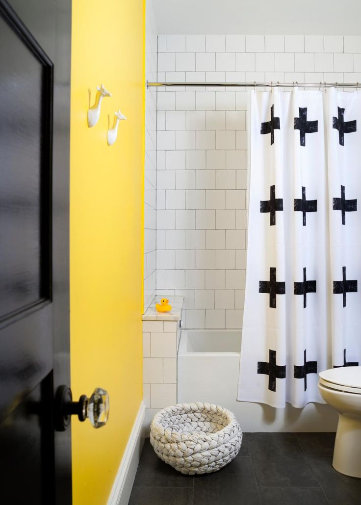 Say hello to yellow - Look how bright and cheerful this family bathroom a child-friendly aesthetic with a fun colorful wall. The vibrant hue of yellow anchors the vintage white subway tile in the shower.