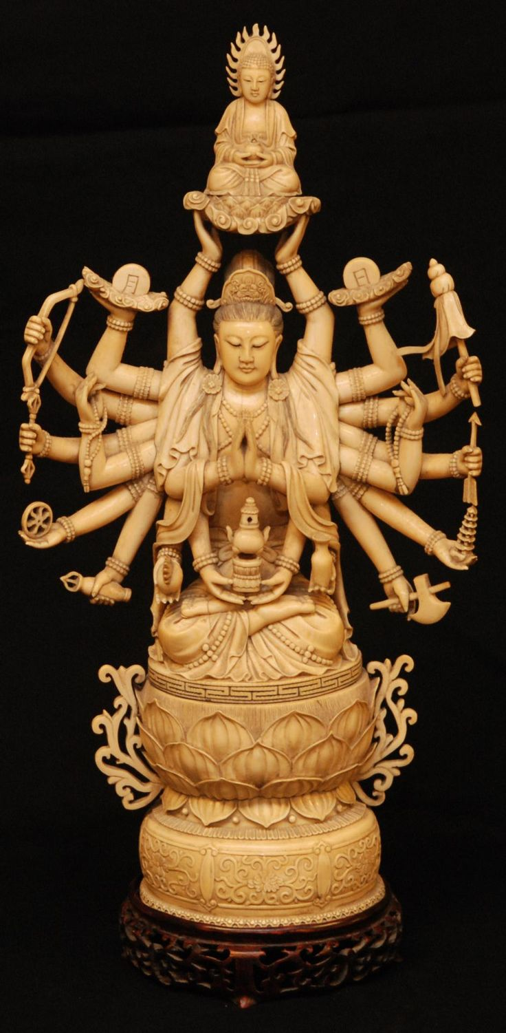 """Antique Chinese hand carved ivory 20 arm Guan Yin figure. Finely carved ivory figure depicts quan yin in layered robe with an item in each hand. Two hands are holding up a seated Buddha figure on lotus blossom base. She is in a seated position over stylized lotus blossom base. Holds Calligrahpy Qian Long mark to bottom. High attention to detail throughout. 18th/19th century. Has fitted wooden base. Measures 20"""" height x 10 1/2"""" width + 1 5/8"""" base height"""