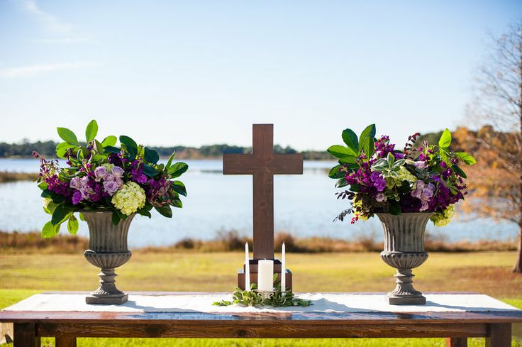 a wood cross and two urns set on  varnished wood table for this outdoor lakeside wedding.the urns are arranged with hydrangea, purple stock, lavender roses,purple and lavender carnations, lemon leaf and variegated pitisporum.