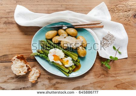 Light spring lunch on the plate. Fried asparagus, fresh potatoes and poached egg with parmesan cheese. healthy food.