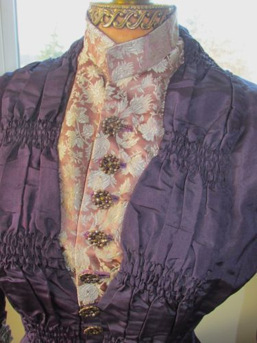 "1880s: ""silk taffeta, frosted lavender and cream rose jacquard trim, creamy lace, cut and faceted metal buttons (18 total), a bounty of pleating, ruffles, bows, tiny hand sewn ruching, dramatic lobster tail train with rows and rows of ruffles, fitted sleeve, ruched shawl collar with mandarin styling, pleated and pointed double layer tails on the bodice with matching button accents, pleated crinoline and lace at the underside of the hem with gorgeous details everywhere you look."" -Ebay"