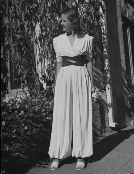 A woman models a very chic white jumpsuit with a wide belt at the Palm Springs Country Club, 1939.