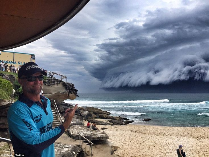 An amused Tamarama lifeguard points out the terrifying cloud in an unbelievable image, as the storm moved across the previously sunny beach
