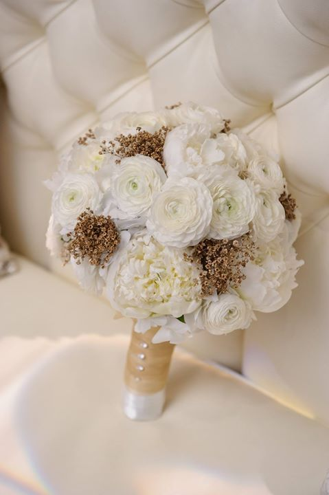 Baby's breath sprayed with gold adds a metallic touch in a bridal bouquet with bright white peonies and ranunculus blossoms ~ https://www.insideweddings.com/weddings/new-years-eve-wedding-with-glittering-metallic-details-in-chicago/787/