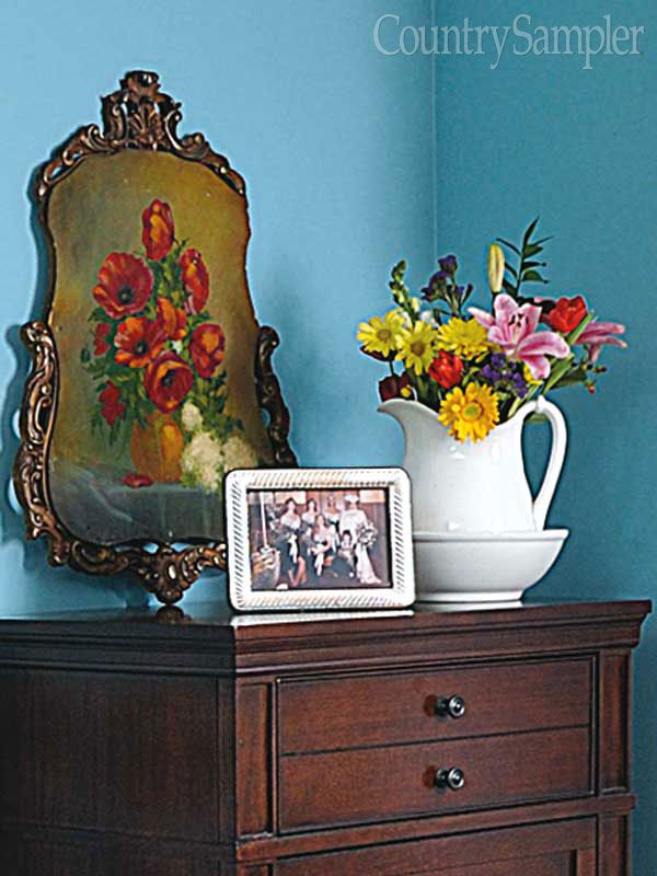 Beautify a bedroom with a colorful arrangement set inside a white ironstone pitcher and washbowl. Set the bouquet near a vintage floral painting and a family photo for a sweet dresser-top vignette.