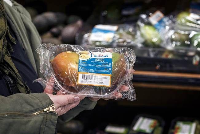 Kaksi mangoa on pakattu ensin muovirasiaan, joka on päällystetty vielä muovikääreellä.
