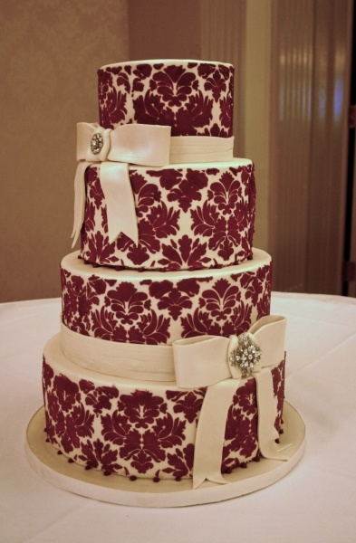 4 tier ivory fondant wedding cake with red damask pattern, and bows made of sugar. By Pearles Specialty Cake Co.