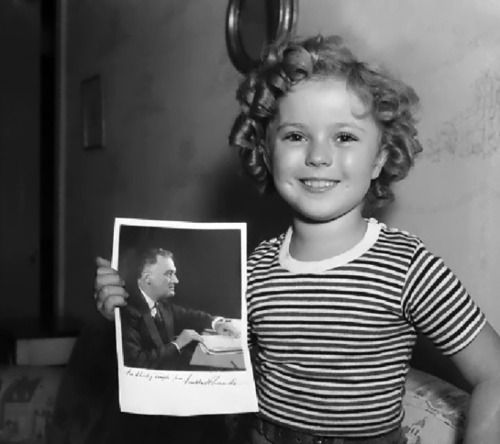 Shirley Temple with a photo of President Roosevelt which he autographed for her - 1935