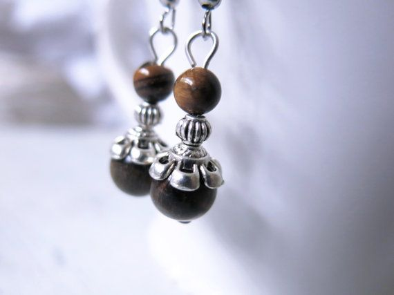 These beautiful handcrafted earrings are made from silver fish hooks featuring elegant 10mm spheres of tigers eye gemstones stacked with tibetan