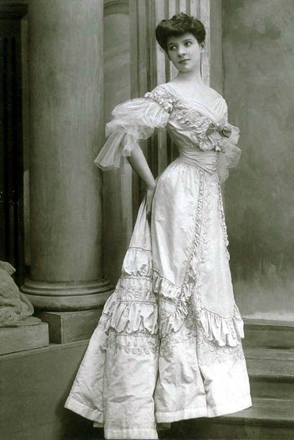 Evening gown, Worth, 1905. Bright floor-length dress in silk taffeta, tone on tone embroidered with rose pattern. The narrow, high waist is accented by an incorporated corset belt. Deep neckline bordered with draped tulle and accented with applied loop. Three-quarter-length sleeves are also made of draped and shirred tulle. Photo: Léopold-Émile Reutlinger. State Museum of Berlin