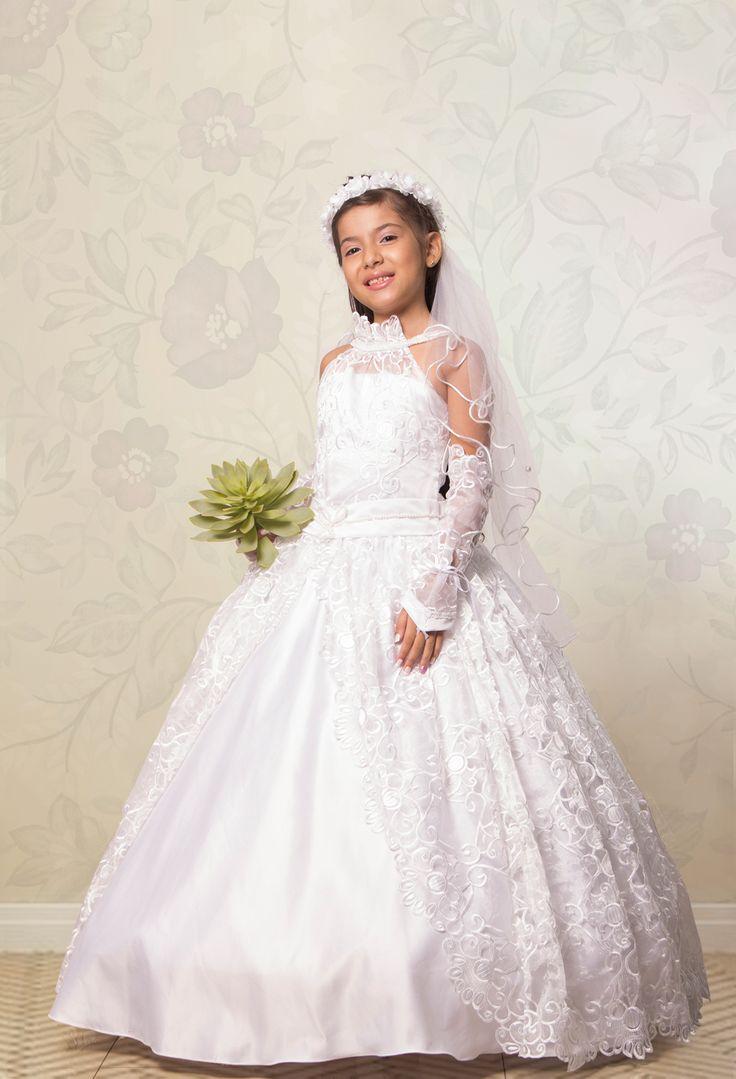 REF.14-32 Vestido de primera comunión, de manga sisa, con cuello alto. Elaborado con tela bordada, con abertura en la mitad de la falda que deja ver la delicada tela satinada. Incluye guantes y velo.