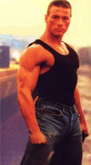 Jean Claude Van Damme standing I tank top showing off muscles.  Possibly Lionheart movie