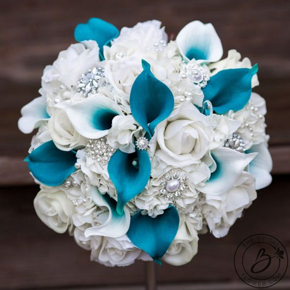 "The Real Teal"" Real Touch hydrangea, calla lily, and rose bouquet with jewels and brooches  This elegant jeweled wedding bouquet in teal and white has got it all, from hydrangeas to calla lilies, and lets not forget about the beautiful brooches! What more could you ask for? Real touch flowers look and feel real, and will photograph amazingly. Easily eliminates an element of stress on your special day because these flowers will look fresh from morning til dusk, and forever after! Splashes of…"