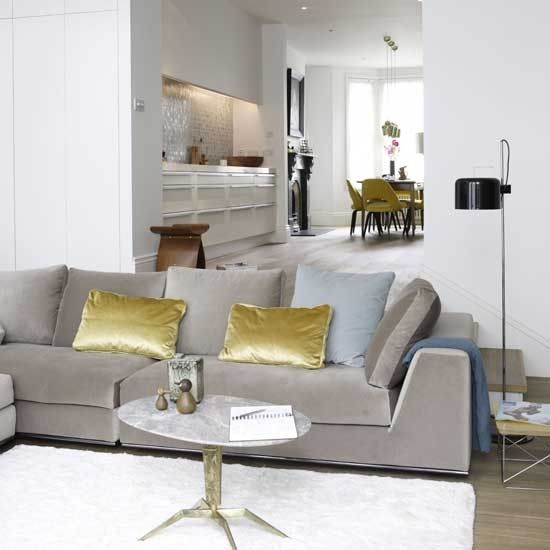 Gold velvet cushions on grey sofa in open plan eclectic living room. Perfectly neutral.