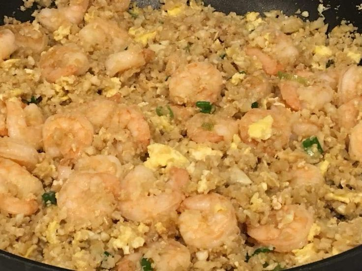 """Cauliflower shrimp """"fried rice"""" is a tasty healthy twist of the Chinese shrimp fried rice. This complete meal allows you to combine your 2 cups of veggies and protein in one delightful dish."""
