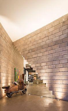 Na parede inclinada da entrada, foram usados dois padrões de blocos de concreto: bloco?vedação e bloco?canaleta