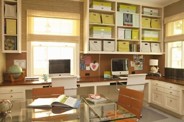 Large office with space with tons of storage and work space. bamboo roman shades, workspace for two, glass desk table, brown walls paint color, desks, shelves, storage, drawers and office chairs.