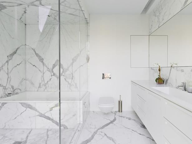 elegant white marble adorns the shower walls backsplash and floor in this crisp white modern bathroom floating toilet and vanity