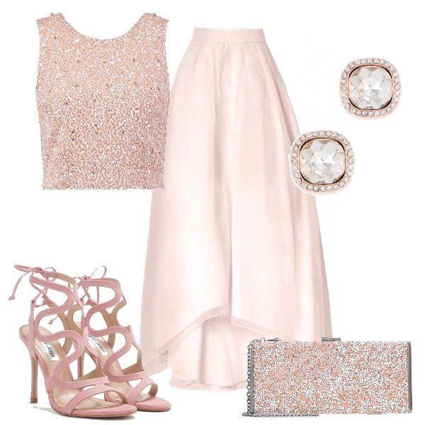 Elegante gonna rosa chiaro, con lunghezza asimmetrica sotto il ginocchio, dalla forma a campana con sottoveste e strato superiore di tulle tono su tono. Top corto rosa, con scollo tondo, senza maniche, completamente rivestito di paillettes. Sandali in nubuk rosa, con tacco a spillo e lacci alla caviglia. Clutch argento e in pietre rosa ed orecchini a lobo dorati e in pietre trasparenti