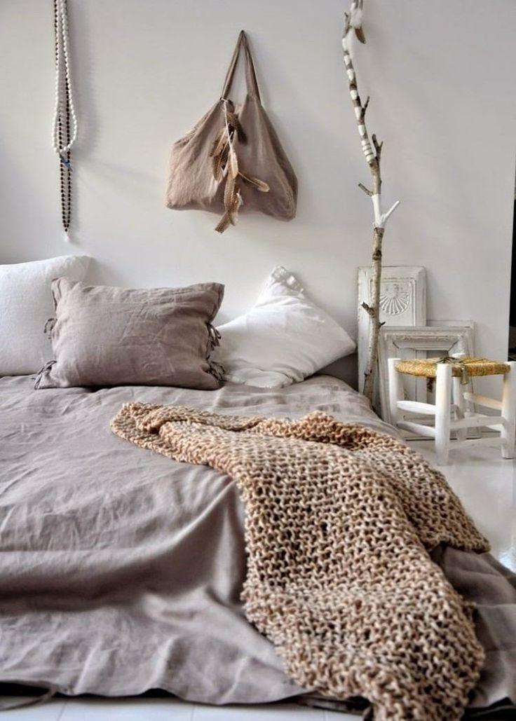 chambre bohème avec une literie en gris clair, couverture tricotée et déco murale en plumes et colliers de perles