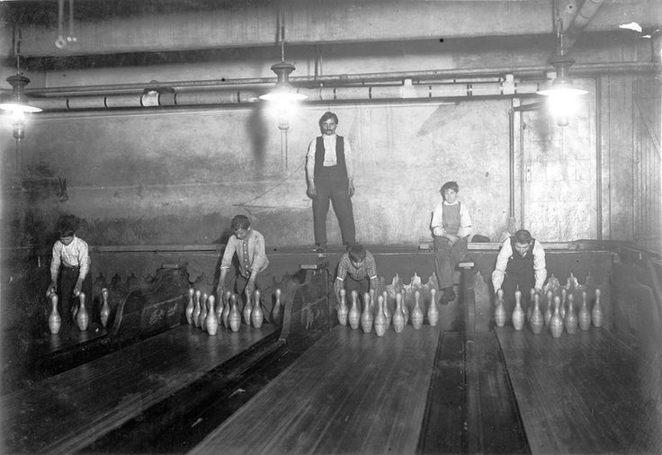 PIN BOYS. It is 1:00 A.M., and the pin are boys working in Subway Bowling Alleys, on South St in Brooklyn. The year is 1910. Before mechanical pinsetter machines were invented in 1936 by Gottfried Schmidt of AMF, pins were set up manually, often by young boys that usually worked past midnight. (A Lewis Hine child labor photo.)