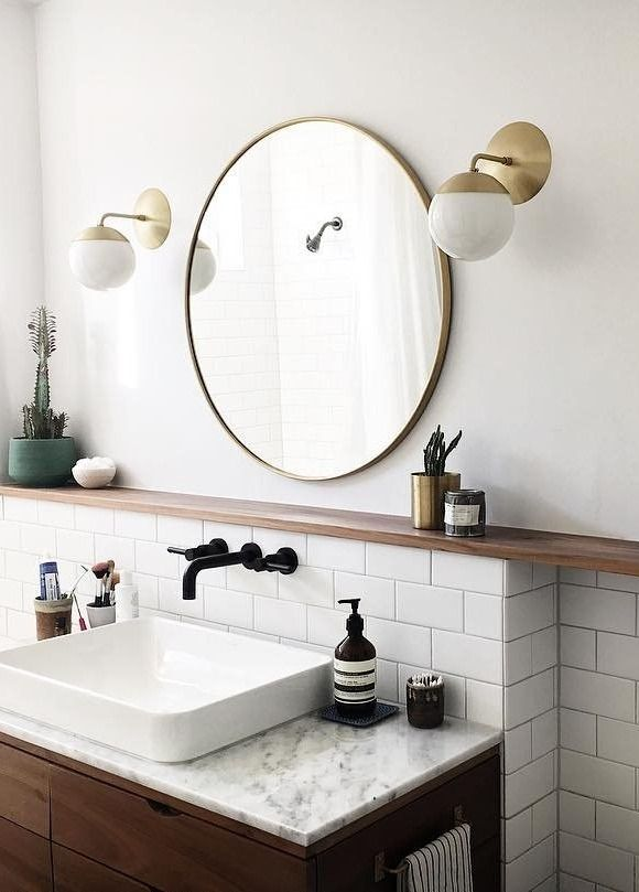 Modern bathroom. White bathroom. Fresh bathroom design. Tile backsplash bathroom. Circle mirror. Round mirror. Mirror with brass border. Round classic framed mirror. Brass mirror. Simple round mirror. White and brass bathroom.