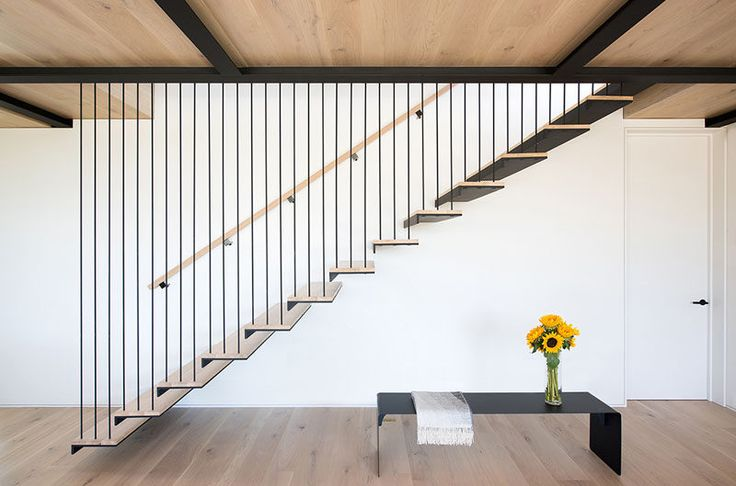 This staircase is strung from steel beams above, and the rods used to support each tread serve as guardrail for the stair.
