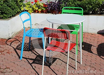Colorful chairs, red, green and blue and white table.