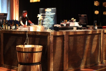 Twelve large wooden bars were built as a gift and then hand stained before forming one large bar in the middle of the venue accessible to guests on all sides.  Half barrels in front held water bottles in ice for those guests looking for a quick drink of water.