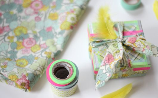 Use washi tape, a feather, some scrap paper and fabric to cover gift boxes to use as a present (by holly becker)