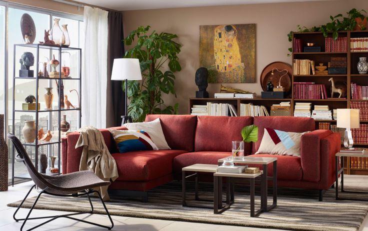 Medelstort vardagsrum med roströd soffkombination med plats för tre personer. Här med tre satsbord och mörkbrun fåtölj av naturfibrer.