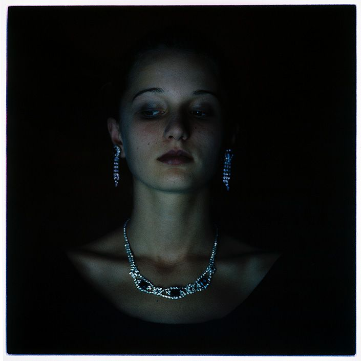Bill Henson. I like the expression this girl has too, and the shadow across her face. It shows off her bone structure and makes her appear more delicate and feminine even though it's such a heavy, dark image.