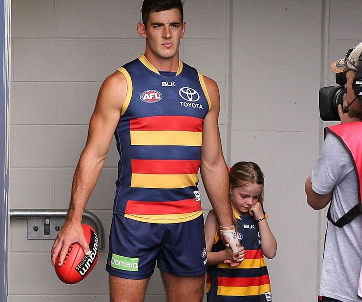 Taylor Walker, captain of the Adelaide Crows walking a young girl overwhelmed by the crowd onto the field.
