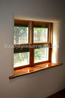 Double hung windows, featuring internal window blinds treatments, are showcased with the east Texas red cedar window sill.