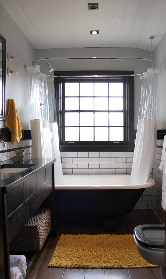Black and yellow accents. Clawfoot tub + shower, subway tile, reclaimed wood floors, small bathroom
