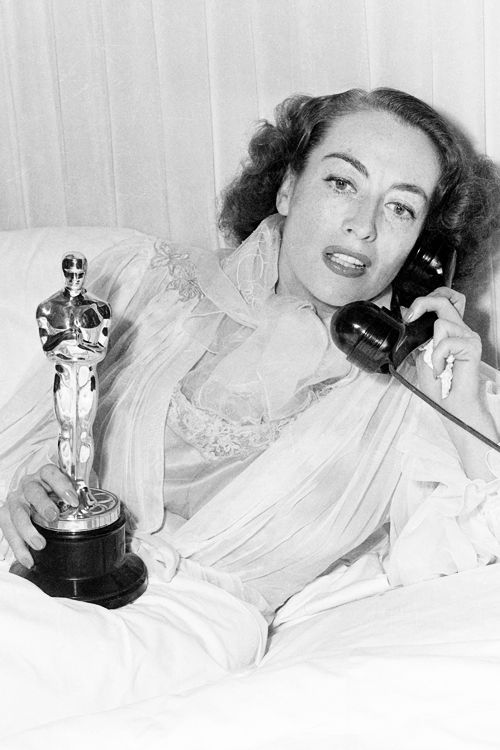 Joan Crawford with her Academy Award for Best Actress for her performance in Mildred Pierce, March 1946. She had been too ill to attend the ceremony and so the award was brought to her.
