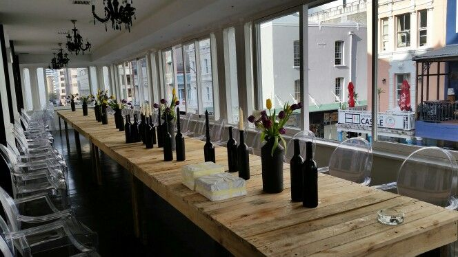 Wedding in th city.  Love the contrast of the raw wood table with the matt black vases and bottles.  Tulips worked really well with the design of the vases