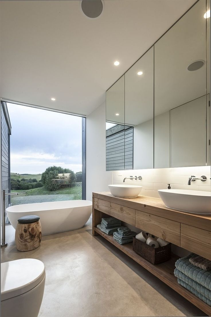 This large bathroom with a great vista, freestanding bath, double vanity and natural materials combine to create a beautiful space.: