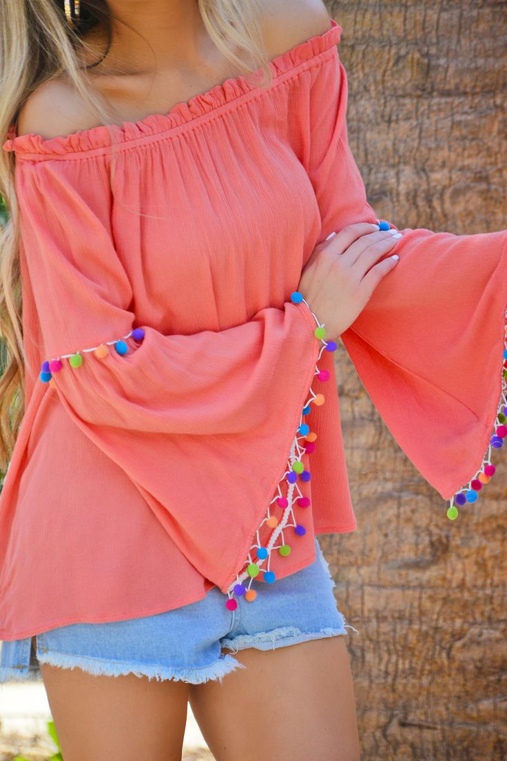 """Stand out in the crowd in the """"Peach Pom Pom Top""""! Colorful pom pom trim makes this top beach ready. An elastic ruffled neckline holds the neckline in place. Fabric is a lightweight 100% rayon."""