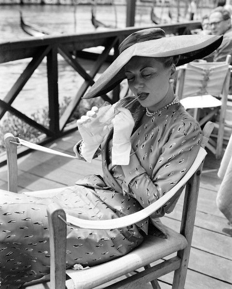 Model in Christian Dior's print two-piece day dress enjoys a cool drink, Venice, June 1951