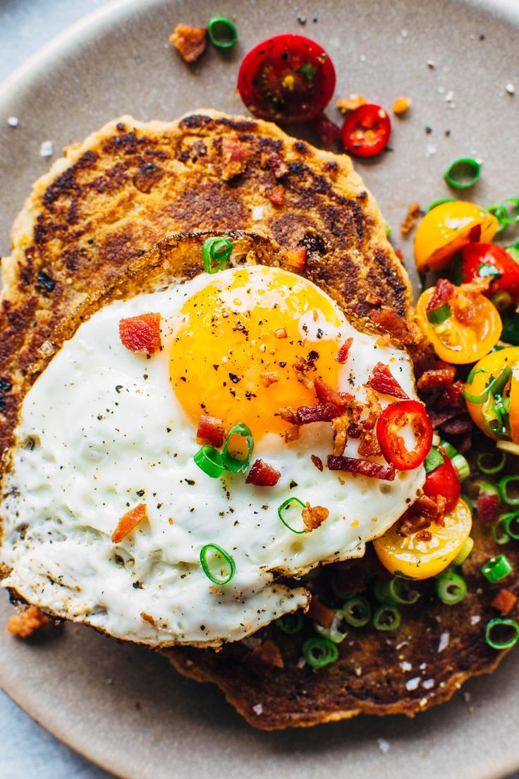 A crazy easy and delicious recipe for savory breakfast pancakes:  made with crumbled bacon, green onions, and topped with a tomato jalapeño salad and fried eggs, these pancakes are the perfect reason to stay home and cook breakfast this weekend.