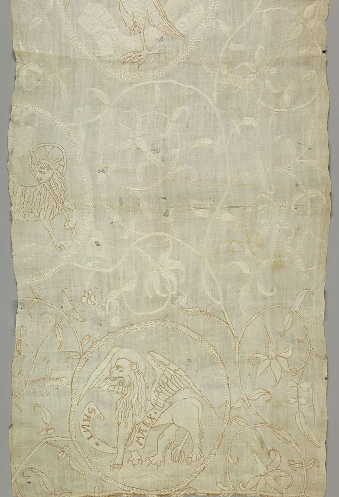 """Not Tudor, but correct time period, for comparison 1550-1600, Switzerland, Cotton on linen Design of foliated scrolls and roundels with the symbols of the four apostles. One roundel shows a lion and the words: """"Sant Mark."""" Two other roundels (incomplete) show portions of the Eagle (St. Mathew) and Ox (St. Luke). A very small part of a brown and white fringe remains at the bottom."""