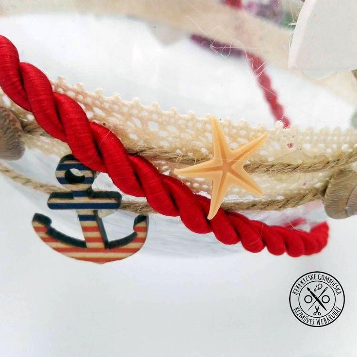Tengerész stílusú gömbváza - 4490 Ft  Gömb alakú üvegváza ekrü csipkével és tengeri dekorációkkal: fából készült hajókormányokkal és vasmacskákkal, kagylókkal, csigákkal, tengeri csillagokkal, saját készítésű gyurma- és kerámia szívekkel, natúr zsineggel, piros kötéllel. A váza méretei: magasság: 10 cm, átmérő: 8,5 cm