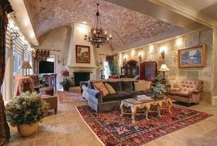 Mediterranean Living Room with Chandelier, stone fireplace, Carpet, limestone tile floors, Wall sconce, Cathedral ceiling