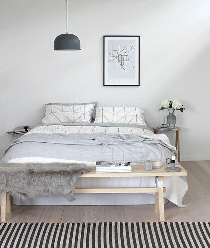 tapis à rayures blanc noir, lit ne bois clair, couverture gris clair, lustre gris
