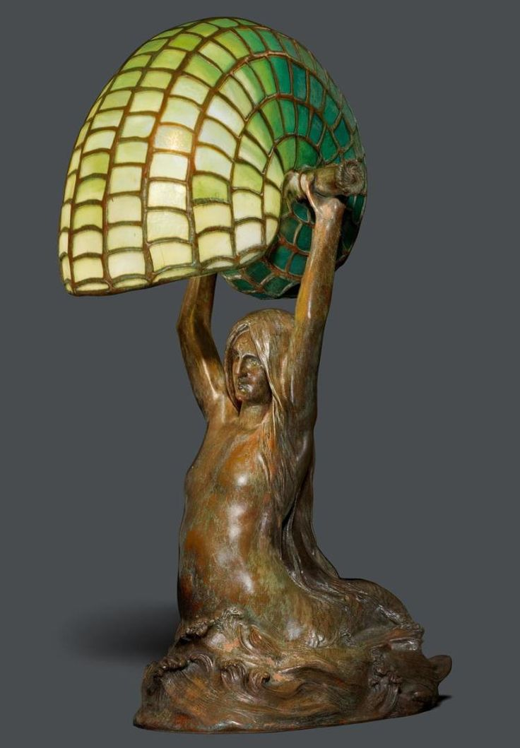"TIFFANY STUDIOS N.Y.<br><br> ""Nautilus/Mermaid"" TABLE LAMP, circa 1910<br>Favrile glass and bronze with a brown patina.<br>The base stamped Tiffany Studios New York, 28631, CLT CO. H. 40 cm.<br><br><br> --------------- <br>TIFFANY STUDIOS N.Y.<br><br>TISCHLAMPE ""Nautilus/Mermaid"", um 1910<br>Favrile Glas und Bronze braun patiniert. Meerjungfrau mit grünem Schirm in Form einer Nautilusmuschel.<br>Boden gestempelt Tiffany Studios New York, 28631, CLT CO. H. 40 cm.<br><br>"