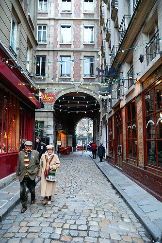 An old couple walking down a cute, cobblestoned passage in the Latin Quarter, Paris.