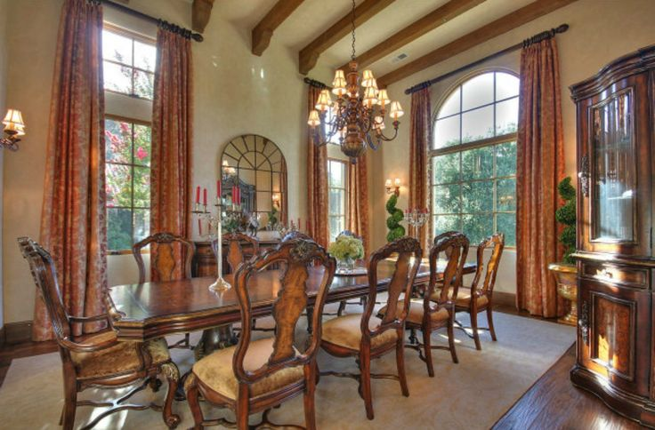 Exposed wood beams above ornate dining set. Chair seats are plush velvet.  Twin topiaries on the far wall and large china cabinet to the right.
