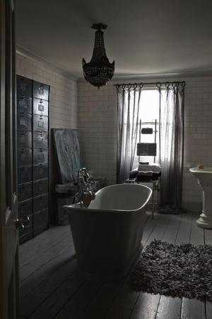 Vrijstaand bad op houten vloer. Een beetje donkere foto maar ik vond deze badkamer door zijn accessoires toch wel heel leuk om mee te nemen. Op de geschilderde houten vloer ligt een lekker dik vloerkleed, ik voel hem al onder mijn blote voeten! Een kroonluchter lijkt overdreven in een badkamer, maar hier staat hij heel goed!